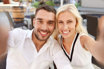 happy couple taking selfie at restaurant terrace