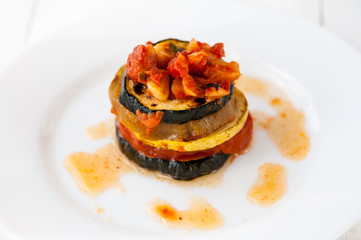 A white plate with ratatouille