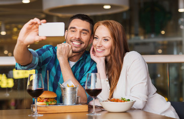 couple taking selfie by smartphone at restaurant