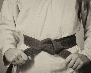 Martial arts Master tightening black belt. Retro black and white toning