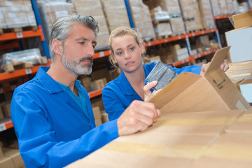 Man and woman in warehouse looking into cardboard box