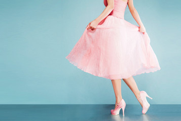 Romantic pink dress with pink shoes on vintage look blue background.