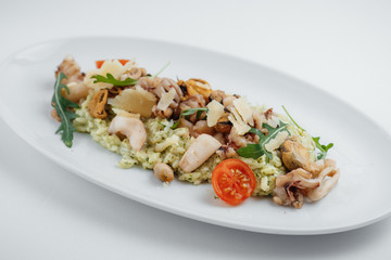 risotto with seafood, tomatoes and arugula on a white plate