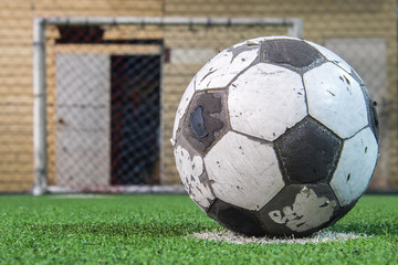 Old ball on the lawn in front of goal .
