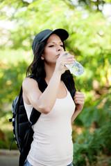 Beautiful woman drinking water while hiking