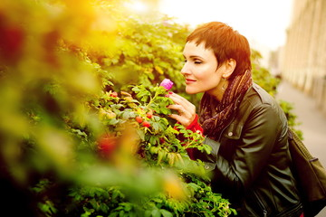 young beautiful woman enjoying the scent of blooming wild rose. The concept of pleasure.