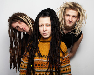 Group portrait of three young freaks with dreadlocks - two boys are looking out behind the girl in fashionable sweater, white background