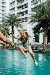 Girl in swimsuit jumping into swimming pool