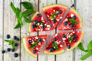 Sliced watermelon pizza with blueberries, mint and feta cheese, above view on rustic white wood