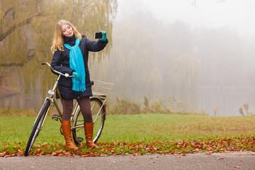 Happy woman with bike in park taking selfie photo.