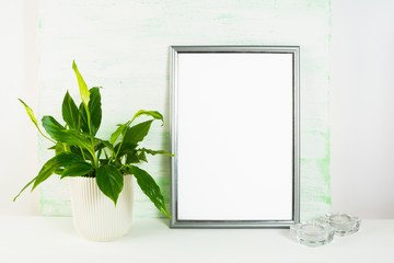 Silver frame mockup with flower pot and candles