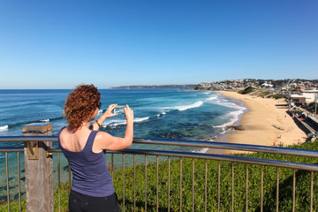 Woman takes a photo of Bar Beach - Newcastle Australia with her phone camera.