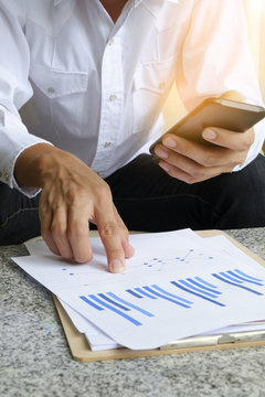 businessman holding mobile phone with analyzing financial chart