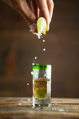 Squeezing lime into shot of tequila. Selective focus. Blurred background.