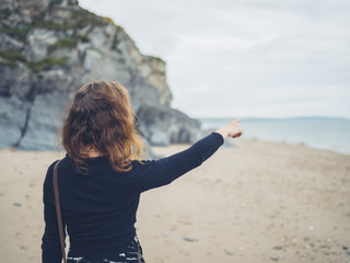 Woman at the beach pointing at the sea