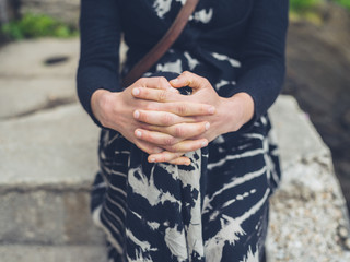 Folded hands of young woman