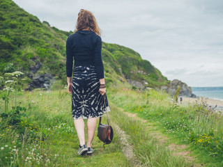 Young woman with handbag in nature