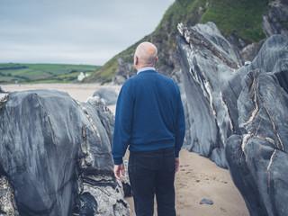 Senior man exploring rocky beach