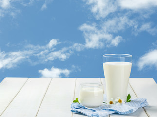 Two glass of milk with Napery on a white wooden table on a blue