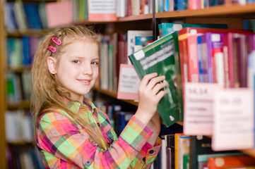 young girl chooses a book in the library