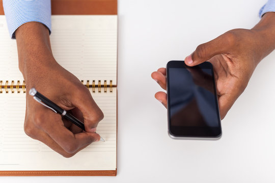 Man hand holding smartphone and writing