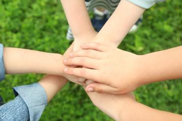 Children holding hands together on grass background