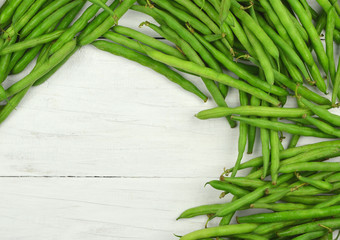 The pods of green beans on the wooden background. Vitamins.