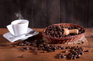 small white cup with aromatic coffee and beans on canestrino