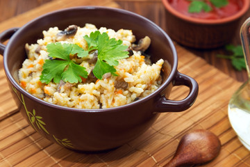 Rice with mushrooms and carrot or pilaf on wooden rustic table.