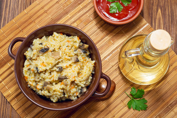 Rice with mushrooms and carrot on wooden rustic table. Olive oil