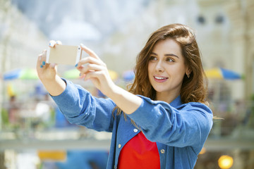beautiful, smiling woman take a picture of herself with a smartp