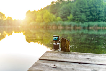 Action camera shoots sunset panorama of the sun on a background of a forest lake.