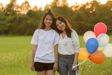 young asian woman two people on green grassland with colored bal