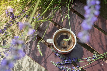 coffee cup outside surrounded by lavender