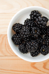Blackberries in a white plate on a wooden board