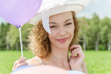 portrait of a girl with a hat and balloons in nature