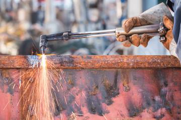 Worker cutting steel using metal torch