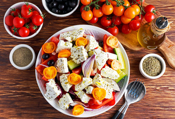 Greek salad with fresh sweet pepper, red onion, orange cherry tomatoes, cucumber, black olives and feta chees drizzled extra virgin olive oil on wooden table