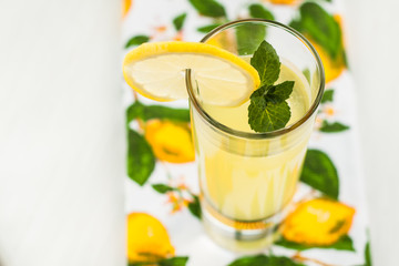 Lemonade in carafe and glasses on the table with mint