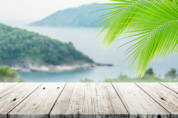 old wood table top on blurred beach background with coconut leaf