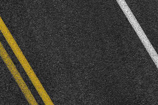 Level asphalted road with a dividing white and yellow stripes. The texture of the tarmac, top view.
