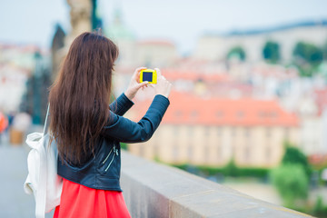 Tourist girl taking travel photos by famous attraction with smartphone on summer holidays. Young attractive tourist taking photo with mobile phone outdoors enjoying holidays travel destination in