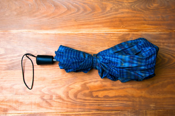 Blue patterned umbrella on wooden background
