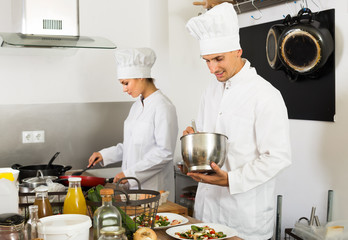 Two adult female and male glad cooks