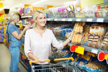 Mature woman choosing pastry in supermarket
