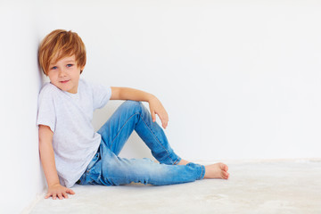 handsome young boy, kid sitting near the white wall