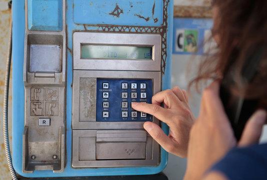 mujer llamando en cabina telefónica
