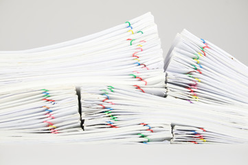 Pile overload report with colorful paperclip place on white background