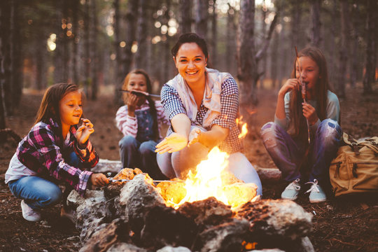 Children by the fire in autumn forest