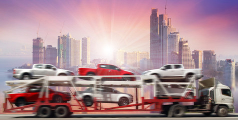 blur motion of trailer transports cars on highway with big city background